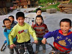 Funny Asian children from rural areas of China, ride bikes. Stock Photos