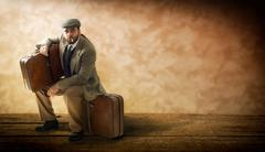 Emigrant with cardboard suitcases. - stock photo