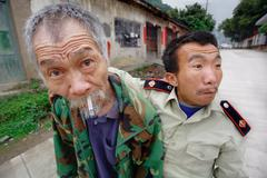 Chinese with cigarette, his friend in uniform, Fuli, Guangxi, China. Stock Photos