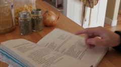 A woman with recipe book and ingredients Stock Footage