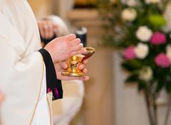 Catholic priest granting the Communion Stock Photos