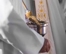 Catholic priest with holy water - stock photo