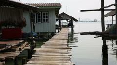 Cleaning net at traditional on stilts fishing village wide shot Stock Footage