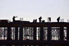 Silhouette of people working and building construction - stock photo