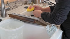 A woman washes dirty dishes in the sink Stock Footage