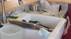 Dirty dishes in a kitchen sink after cooking - stock footage