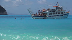 Cruise ship anchored in a blue bay near seashore. Tourists swim around the boat  Stock Footage