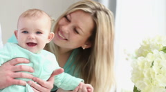 a young family with a baby are at home by the window - stock footage