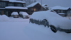Weather, heavy snow on cars and homes, dawn early light Stock Footage
