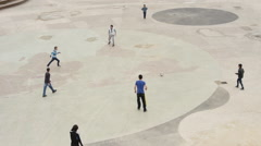 Children, kids are playing football on a concrete city square, area Stock Footage