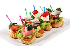 Assorted canapes-sandwiches on plate over white background Stock Photos