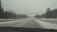 Stock Video Footage of drive plate handheld, passenger POV, Trans-Canada sign winter highway