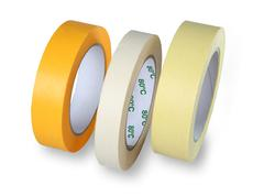 Three rolls of narrow masking tape, yellow, white and brown, standing at his  - stock photo