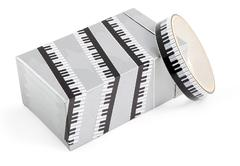 A box wrapped in decorative adhesive packaging tape with print piano. Adhesiv - stock photo