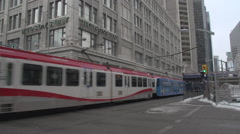 LRT trains passing on a cold grey day in Calgary, 1st St and 7th Ave SW Stock Footage