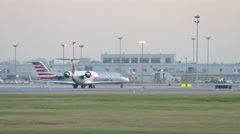 4K UHD - American Eagle CRJ taxiing with airport tower at dawn Stock Footage