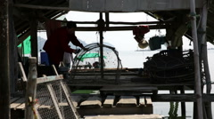 Cleaning net at traditional on stilts fishing village Stock Footage