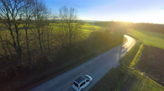 Stock Video Footage of Aerial of vehicle driving towards the sunset 4K