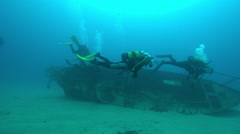 Divers swimming over shipwreck near seabed - stock footage