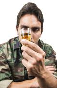 distraught military soldier veteran ptsd drinking a shot of liquor - stock photo
