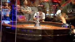 People playing roulette in casino, shot behide glass Stock Footage