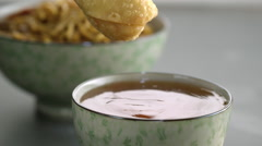 Appetizer being dipped in sauce - stock footage