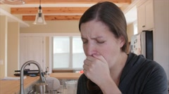 A sick woman blows nose in kleenex Stock Footage