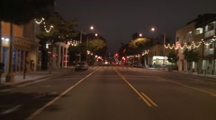 A car travels along a street at night in Santa Monica, California as seen Stock Footage