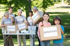 Happy siblings holding donation box Stock Photos