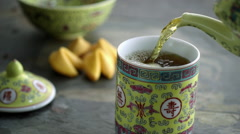 Green tea being poured in yellow cup Stock Footage