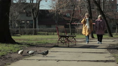 Two women walking in the park and pigeons pecking slice of bread and crumbs. Stock Footage