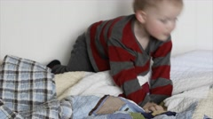 Toddler jumping on a bed in his bedroom Stock Footage