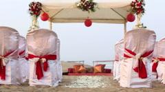 Wedding decorated tent spectators seats rose petals on ocean sand shore Stock Footage