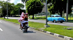 Cuban couple riding a motorcycle Stock Footage