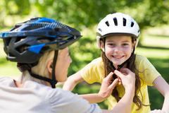 Mother attaching her daughters cycling helmet - stock photo