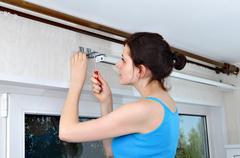Girl hangs vertical blinds, tighten with a screwdriver, screw brackets - stock photo