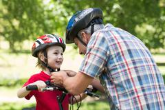 Father attaching his sons cycling helmet - stock photo