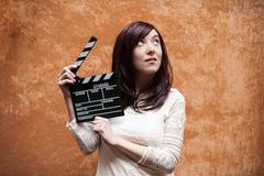 Young woman 70s hippie style closeup with clapperboard Stock Photos
