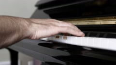 A man playing arpeggios on a piano inside his home Stock Footage