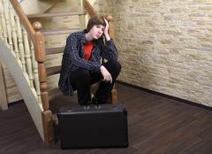 Teenage boy 14 years, sitting on wooden stairs near suitcase. - stock photo