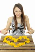 The girl gathered on the table image of the heart of yellow dandelion flowers - stock photo
