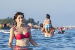 Girl in pink bathing suit standing waist-deep in sea water. - stock photo