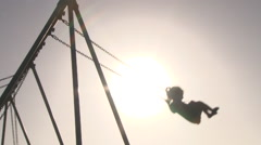 Silhouetted Children Swinging on Summer Day Stock Footage