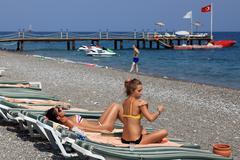 Antalya resort beach with sun loungers, berth, and sunbathers people. Stock Photos