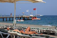 Sunbeds and umbrellas in beach resort, girl sunbath on lounger. Stock Photos