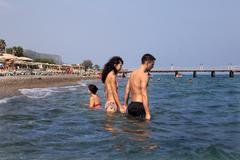 Turkish resort, Couple goes deep into the seawater holding hands. Stock Photos