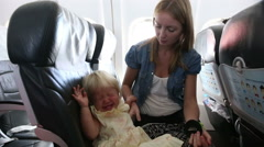 child sits and misbehaves in airplane - stock footage