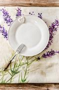Plate and fork on vintage wooden dining table - stock photo