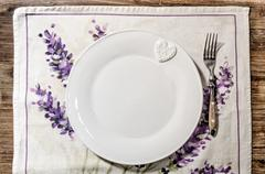 Plate and fork laid on vintage wooden dining table - stock photo