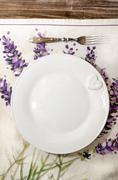 Fork and plate laid on vintage wooden dining table - stock photo